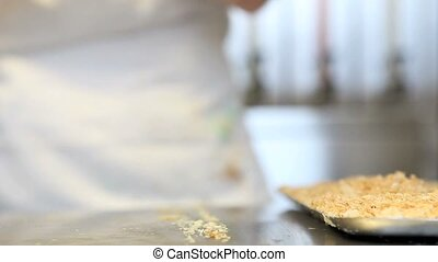 hands finish cake with pastry puff crumbs