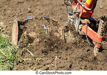 Hand plowing. - Closeup of hand motor plow blade throwing...