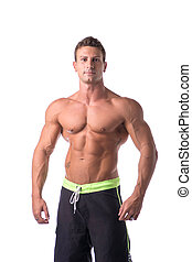 Muscular young bodybuilder in relaxed pose, smiling....