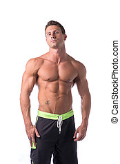 Muscular young bodybuilder in relaxed pose. Isolated on...