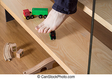 Stepping on toy - Close-up of young man's foot on stairs...