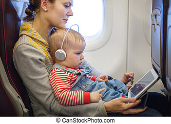 Mother and son using tablet on board of airplane - Caucasian...