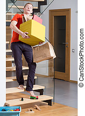 Carrying the boxes - Young careless man on stairs carrying...