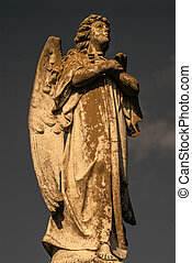 Male Angel Statue - A statue of a male angel holding a...