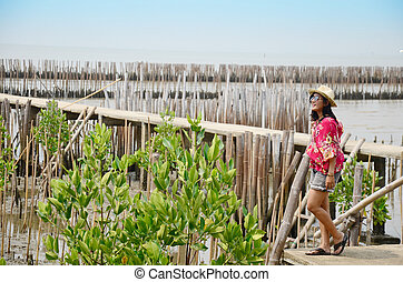 Thai women standing alone on the walkway bridge in Mangrove...