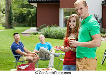 Group of friends on garden party during vacation
