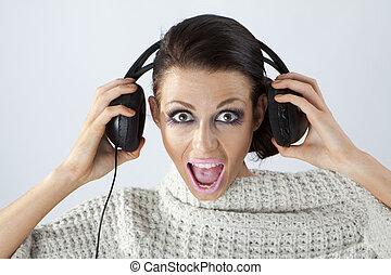 Studio portrait of a girl in headphones listening music
