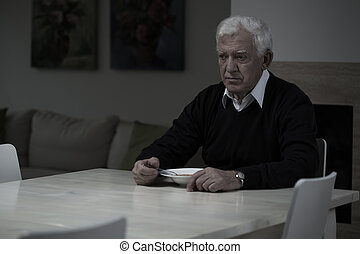 Lonely dinner - Aged depressed man and his lonely dinner