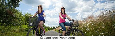 Bicycle trip - Two girls on summer bicycle trip in country