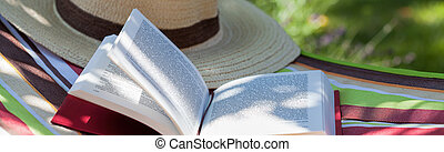 Book and hat - Book and a hat lying on a hammock