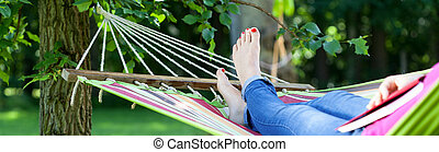 Girl on hammock - Young girl resting on hammock with book...
