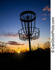 Disc golf basket against sunset