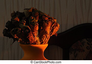 Jug with a bouquet of dried leaves resembling roses, lit the rising sun.
