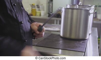 male chef sharpening knife in commercial kitchen