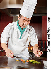 Cook puts vegetables to the dish - High cuisine. Japanese...