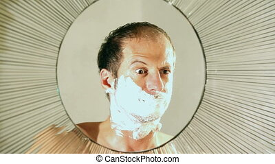man shaving in round mirror