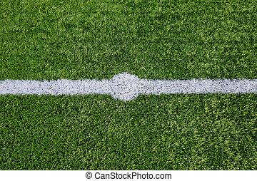 Straight white chalk line marking on grass background.