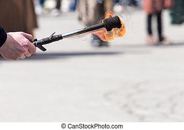ardor in the hands - hand holding a torch ignited during a...