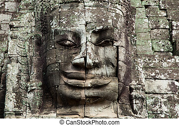 The stone face of the khmer king on the wall of Bayon...