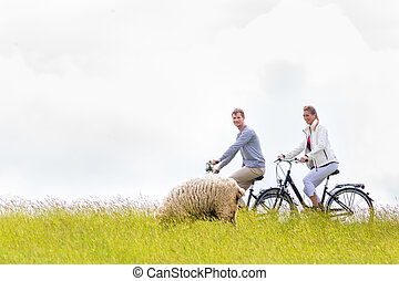 Couple having sea coast bicycle tour at levee - Couple...