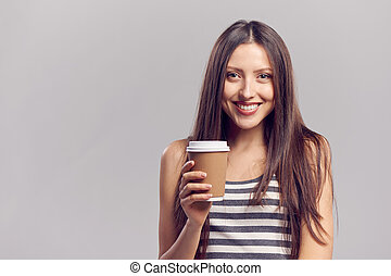 Woman drinking hot drink from disposable paper cup -...