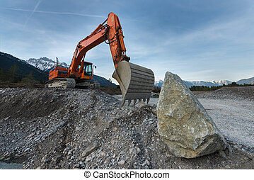 huge shovel excavator standing on gravel hill with stone...