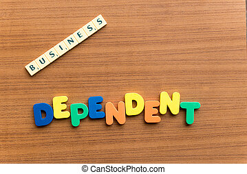 dependent colorful word on the wooden background