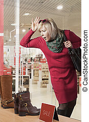 Woman Window Shopper - Young woman looking a shop window at...