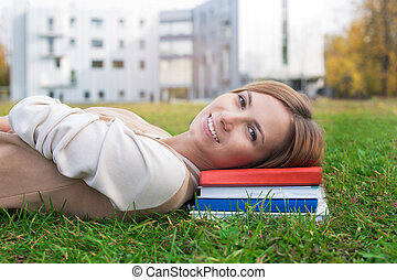 Student lying on green grass and books On the sunset