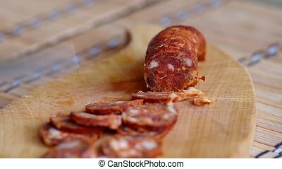Slicing sausage with knife on wooden board