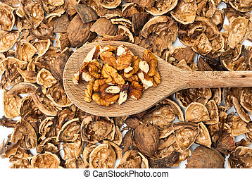 Walnuts on the wooden spoon against nutshell background