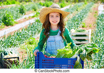 Litte kid farmer girl in vegetables harvest at orchard