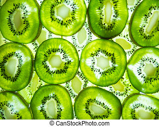 Many fresh kiwi slices lit from below
