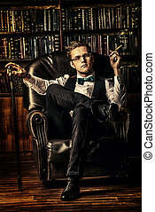 well-groomed man - Elegant young man in a suit sitting in...