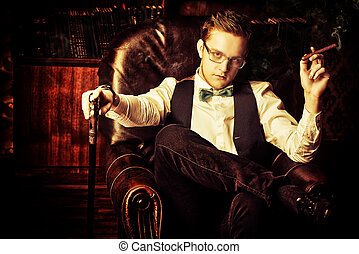 dandy style - Elegant young man in a suit sitting in...