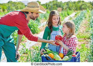 Farmer showing vegetables harvest to kid girls - Farmer man...