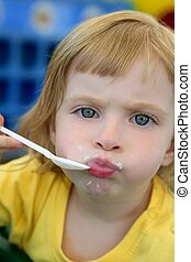 Blond little girl eating and gesturing