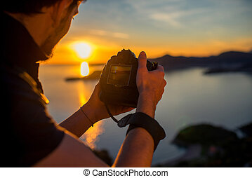 Man photographing sunset on the top of mountain - Man...