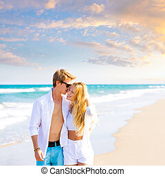 Blond teen couple walking together in the beach