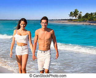 couple young walking in a tropical Caribbean beach