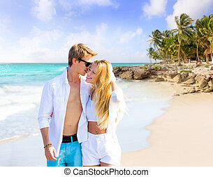 Blond couple walking in tropical Caribbean beach