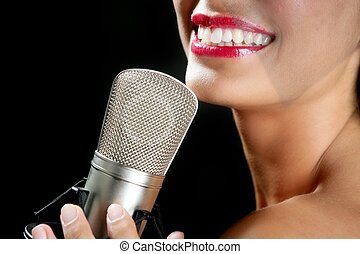 Beautiful woman singing on a vintage microphone on black...