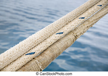 Heavy duty and weathered ropes, attached to the pier for...