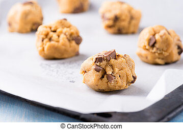 Raw cookie dough on a baking tray with parchment paper,...