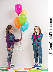 Kids - Best friends. Two cute little girls with baloons on...