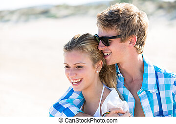 Blond teen couple hug together in beach outdoor