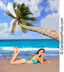 Brunette tourist lying in beach sand tanning happy