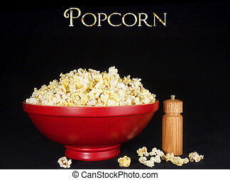 Serve Popcorn - Red wooden bowl filled with popcorn on black...