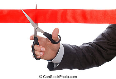 Hand of businessman in suit cutting red ribbon with pair of...