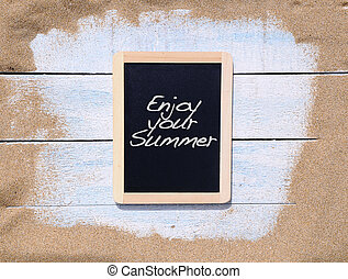 Enjoy your summer - Blackboard on the beach with the phrase...